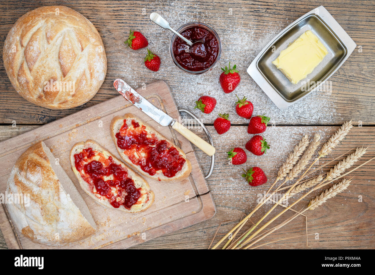 Strawberry jam on bread with wheat and strawberries on a wood background - Stock Image