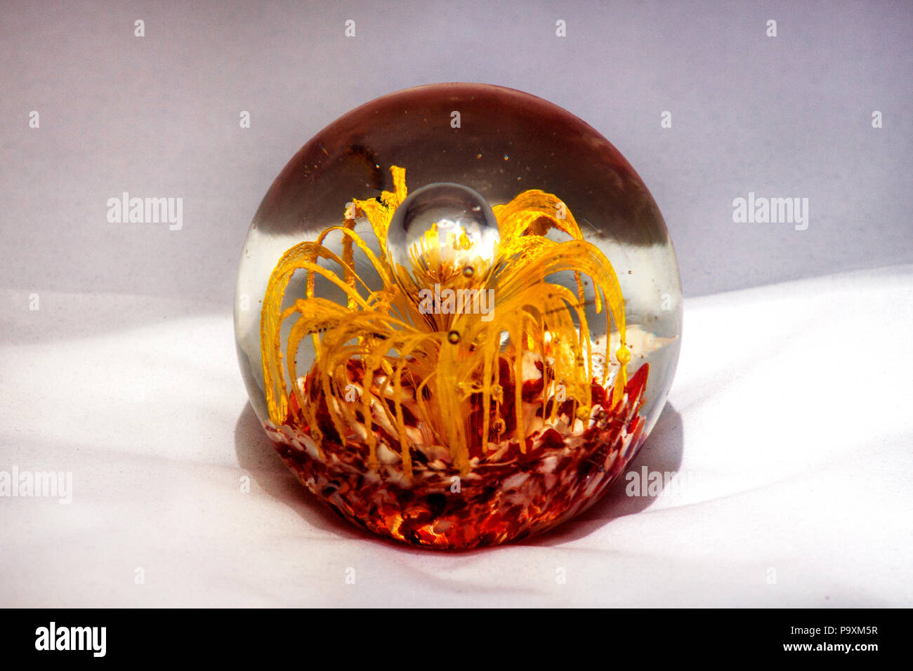 Glass Ball With Yellow And Red Decorative Elements In It Stock