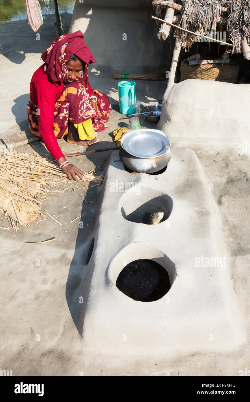 A woman subsistence farmer cooking on a traditional clay oven, using rice stalks as biofuel in the Sundarbans, Ganges, Delta, India. the area is very low lying and vulnerable to sea level rise. All parts of the rice crop are used, and the villagers life is very self sufficient, with a tiny carbon footprint. - Stock Image
