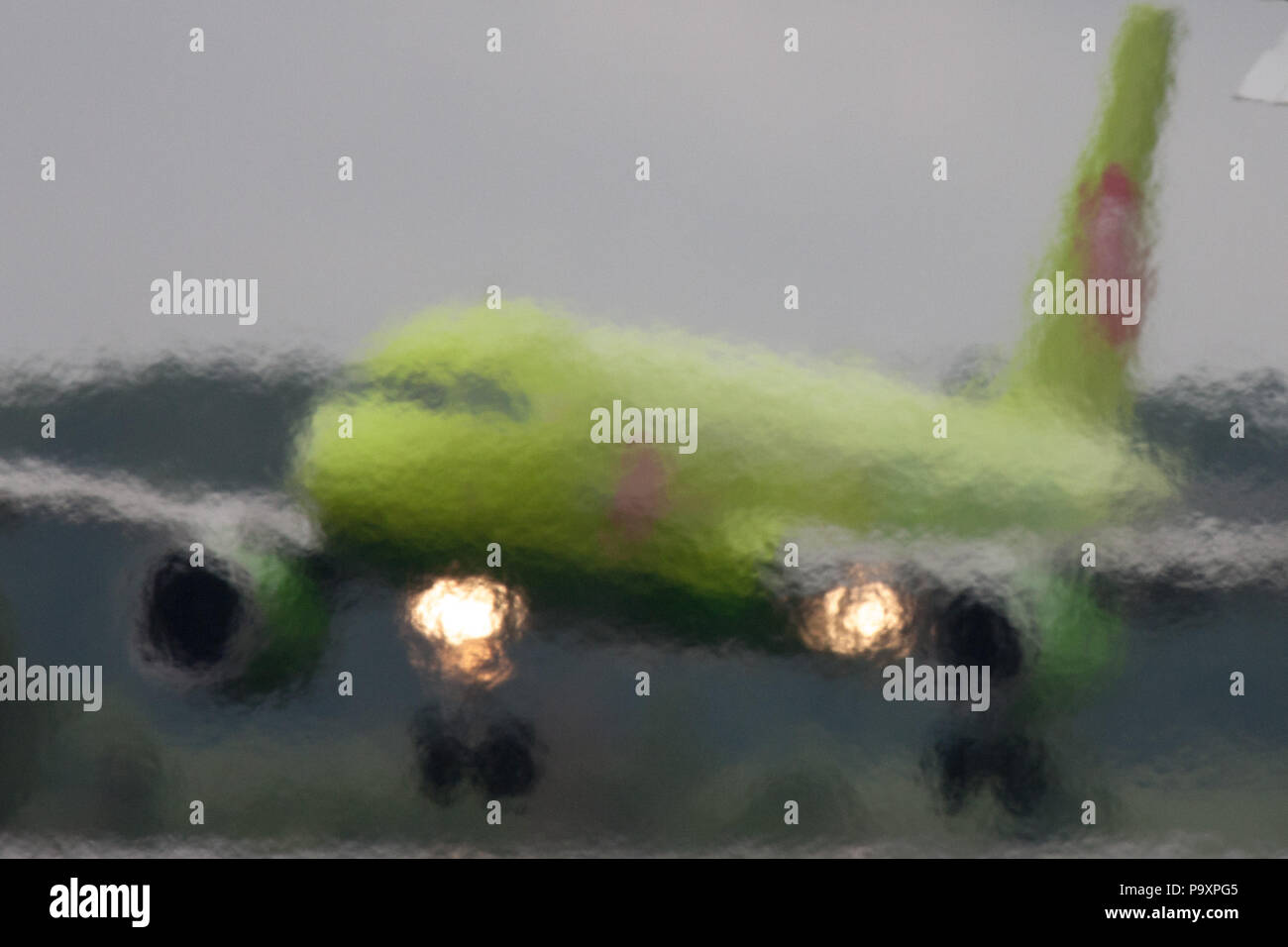 The Airbus A320 of S7 Airlines blurred by the jet exhaust of another airplane lands at Domodedovo airport, Moscow Region, Russia - Stock Image