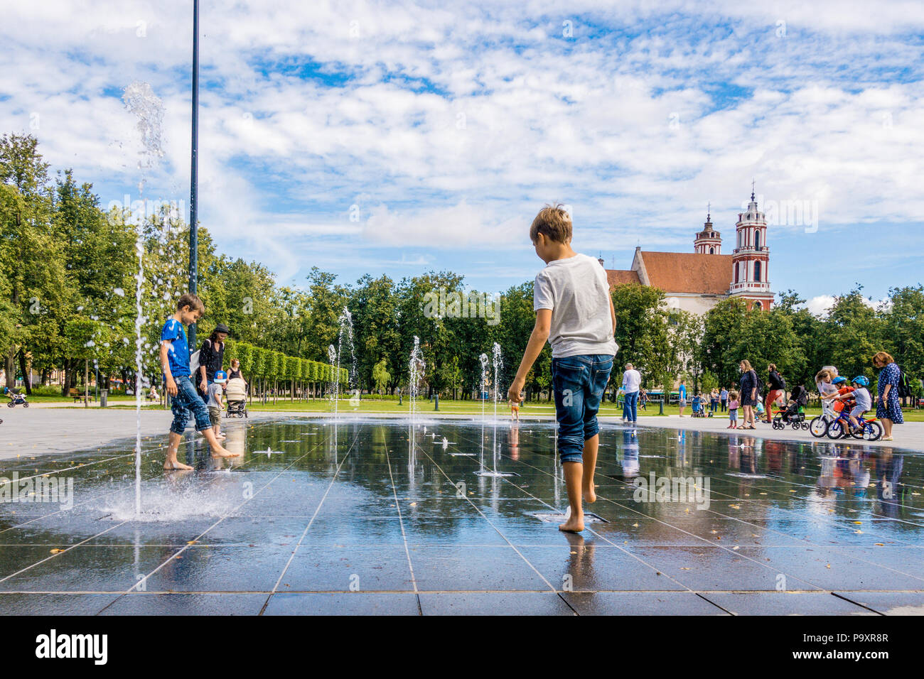 Vilnius Lithuania, July 06 2018: Happy kids have fun playing in city water fountain on hot summer day in Lukiskes square - Stock Image