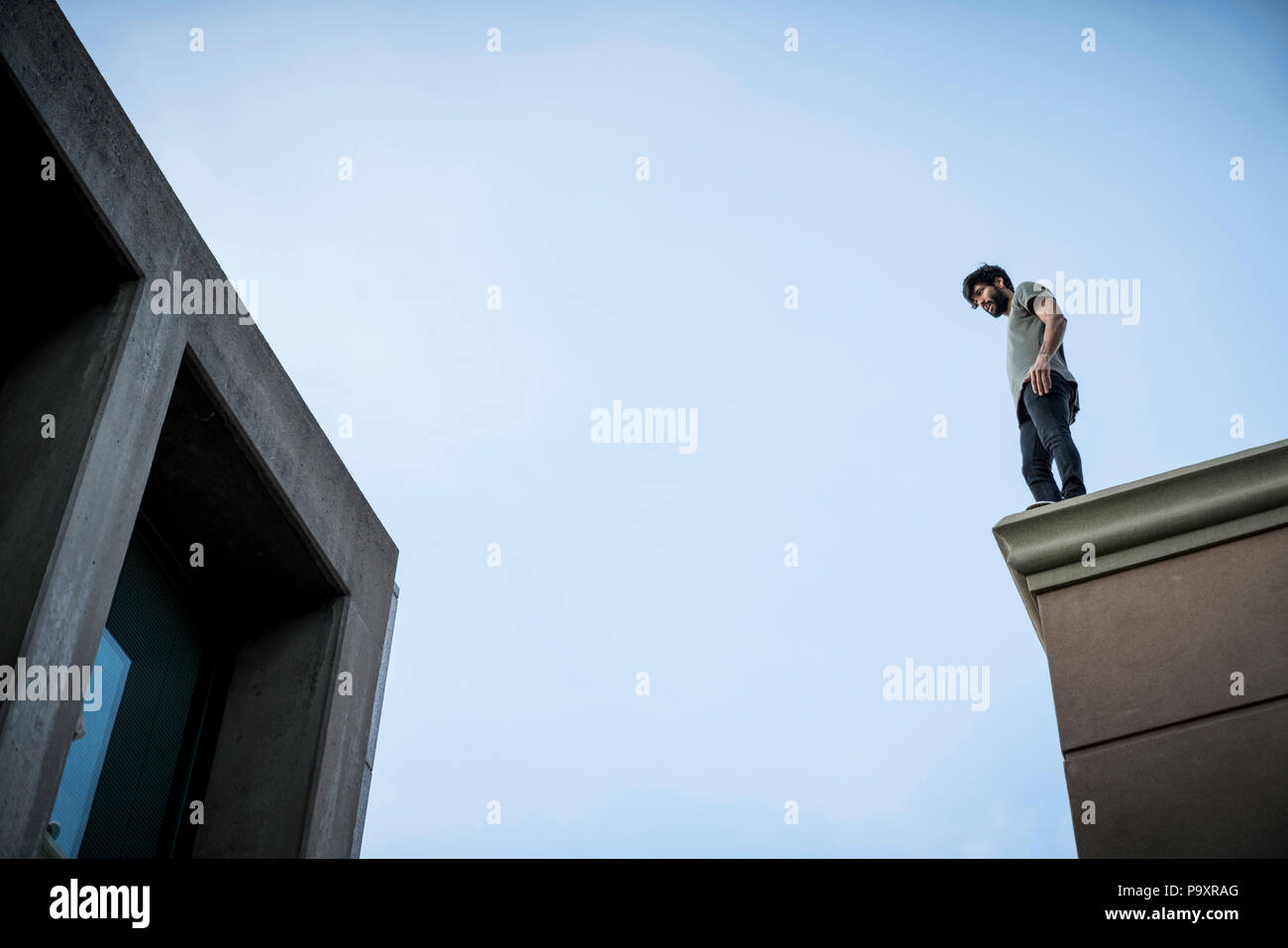 View from below of male parkour athlete standing on roof - Stock Image
