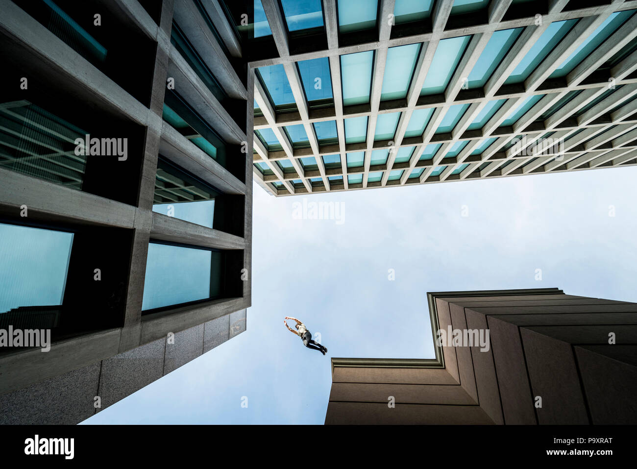 View from below of male parkour athlete jumping from one roof to another - Stock Image