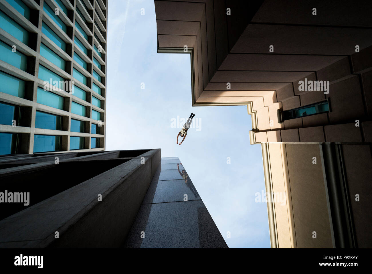 View from below of male parkour athlete jumping from one roof to another Stock Photo
