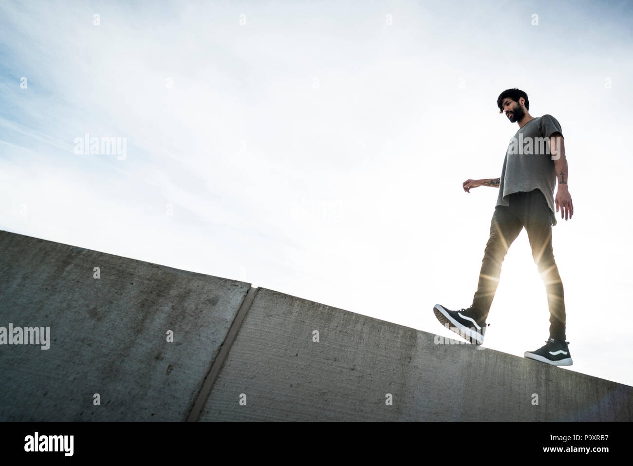 Side view of male parkour athlete walking on top of wall - Stock Image