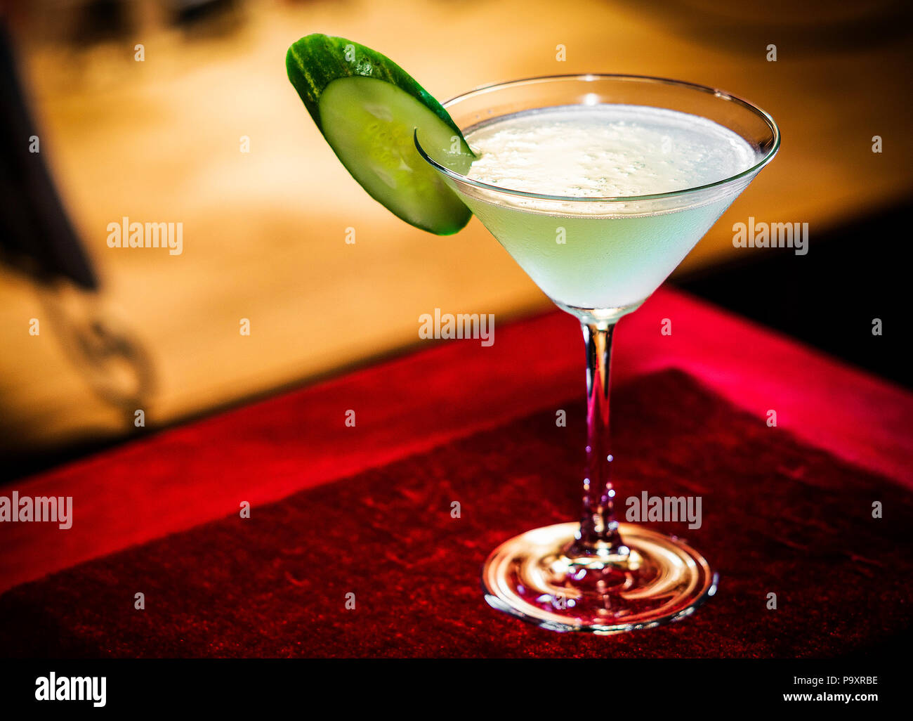 cucumber and lime martini mixed cocktail drink glass inside cozy bar - Stock Image