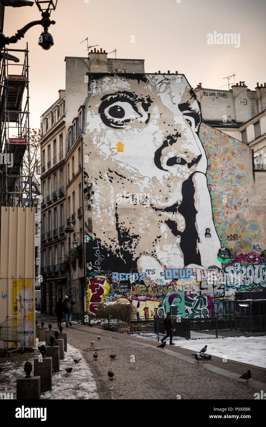 Mural of human face with finger on lips on wall of apartment block, The Marais, Paris - Stock Image