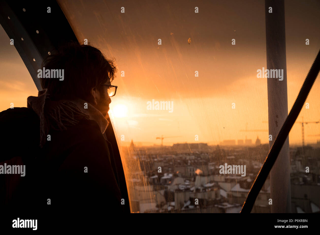 Man looking through window at sunset at view of Paris, France in Centre Georges Pompidou - Stock Image