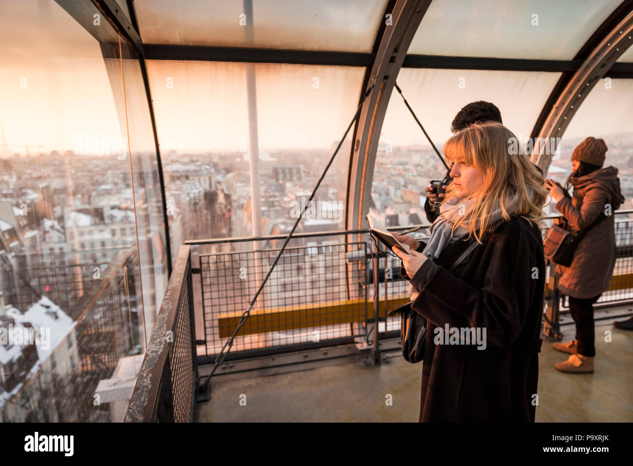 Tourists looking through window at view of Paris, France in Centre Georges Pompidou at sunset - Stock Image