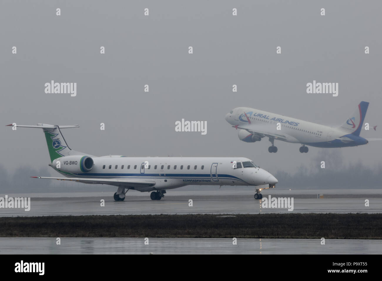 The Embraer-145 regional jet airplane of Komiaviatrans and Airbus A320 of Ural Airlines taking off from Domodedovo Airport, Moscow Region, Russia - Stock Image