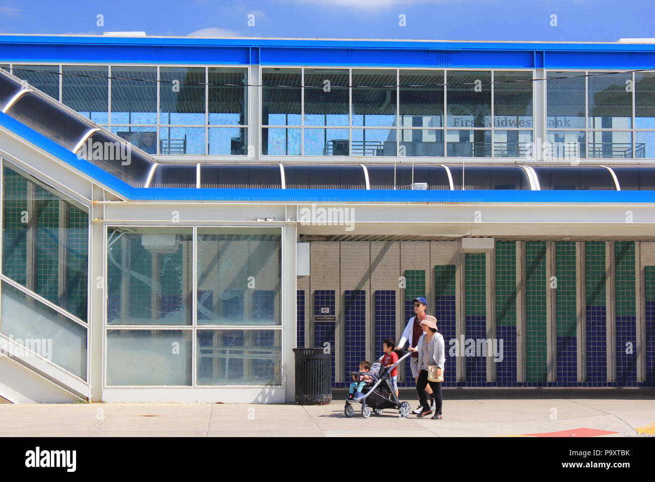 Family pushing a stroller and stopping at the CTA Blue train stop at Cumberland Station in Park Ridge, Illinois on a sunny summer day. - Stock Image