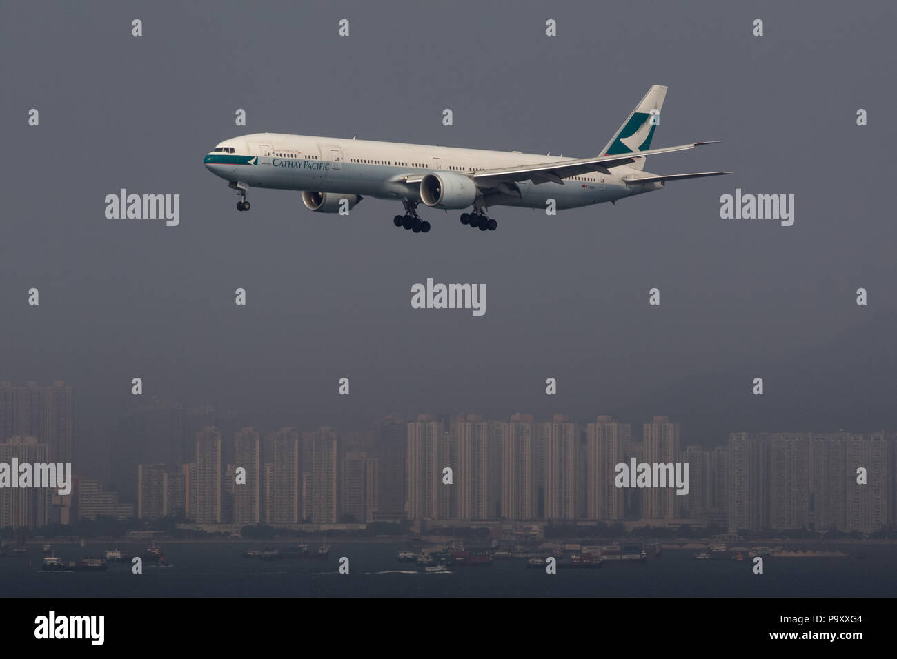 The Boeing 777-300ER widebody civil jet airplane of Cathay Pacific pictured approaching Chek Lap Kok airport, Hong Kong, China - Stock Image