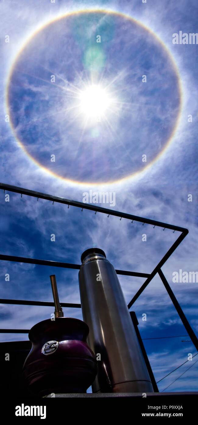 Solar halo in a sunny summer midday. Blue sky with white clouds and an halo with the rainbow colors around the sun. - Stock Image