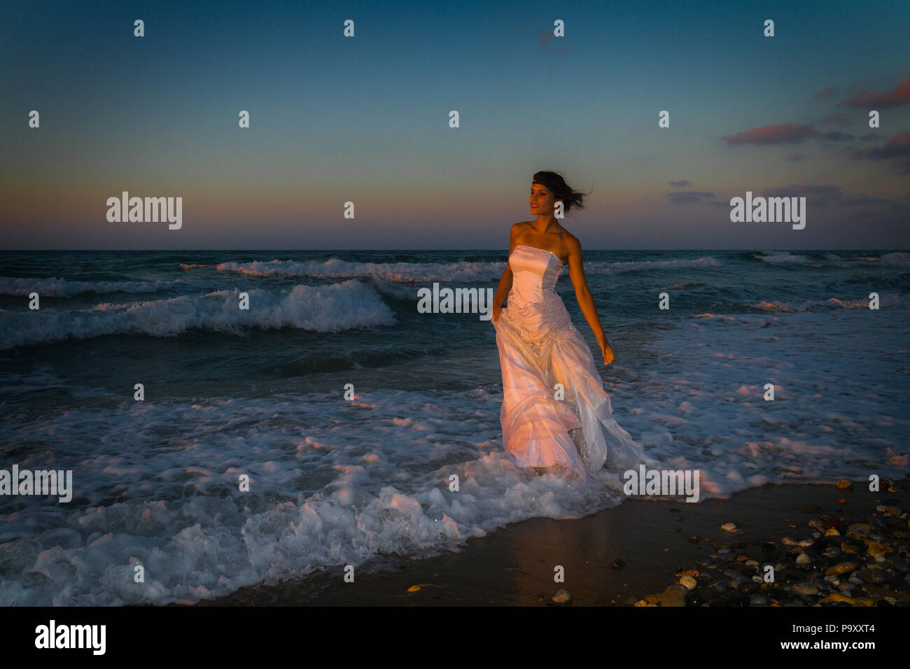 Woman in white dress, barefoot, feeling happy, alive and free in nature meditating at sandy misty beach breathing clean fresh ocean air at dusk. Summer holidays lifestyle concept - Stock Image