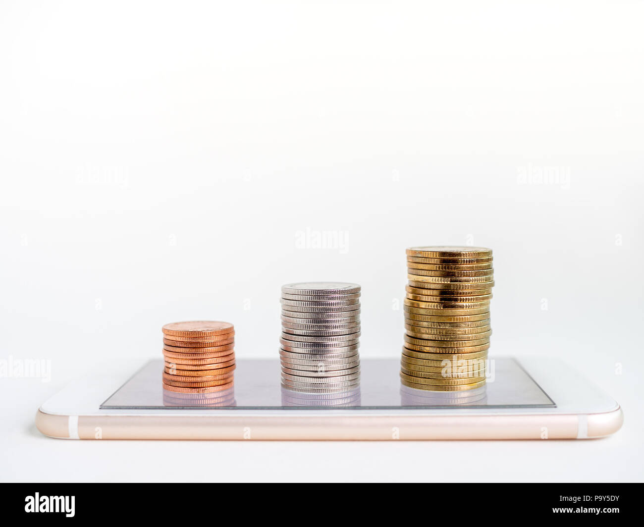 Making money online. Business financial online concept. money, stack of copper, silver and gold coins on mobile Phone isolated on white background wit - Stock Image