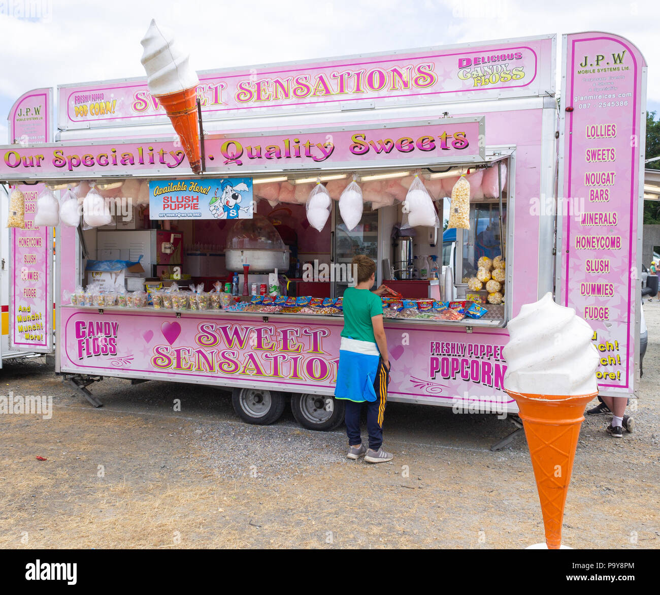 children buying sweets from a showground stall. - Stock Image