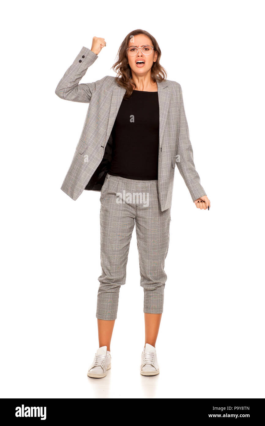 Angry young beautiful woman in a jacket, blouse, sneakers, trousers and glasses - Stock Image