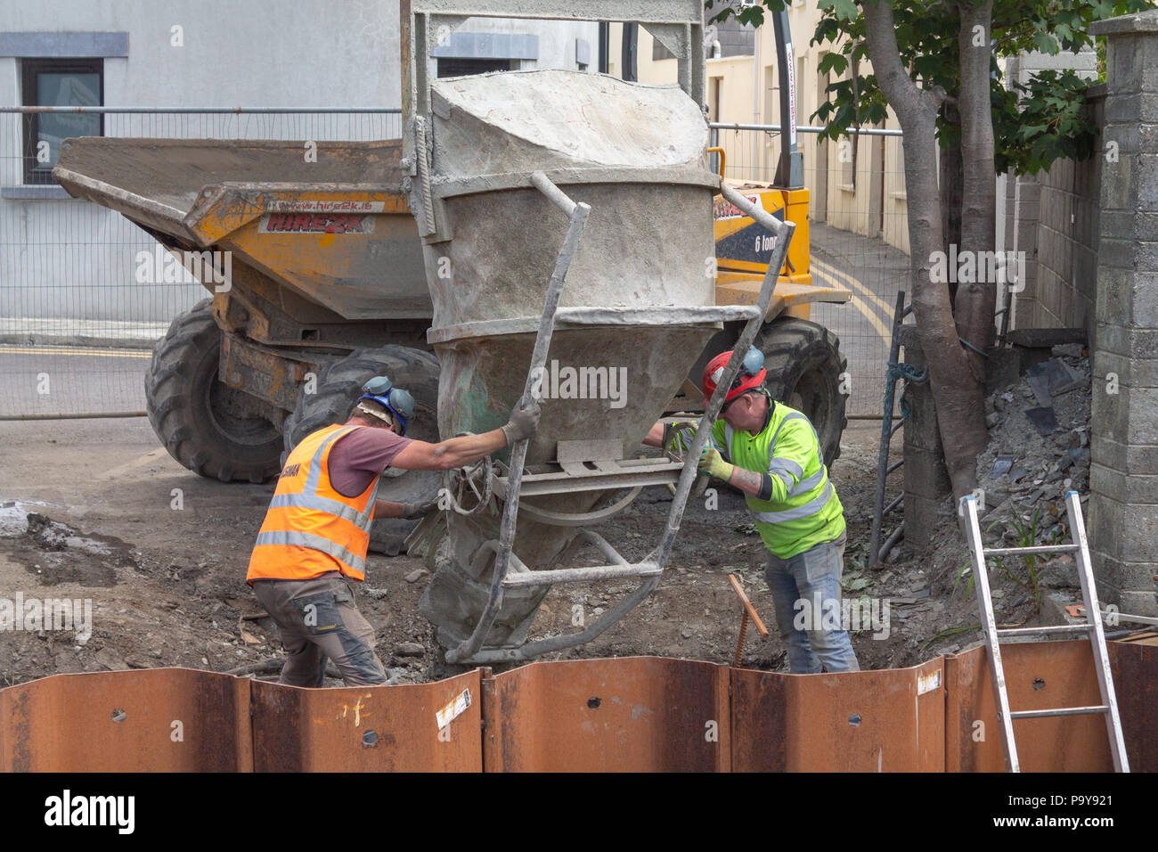 builders pouring concrete into metal shuttering from a