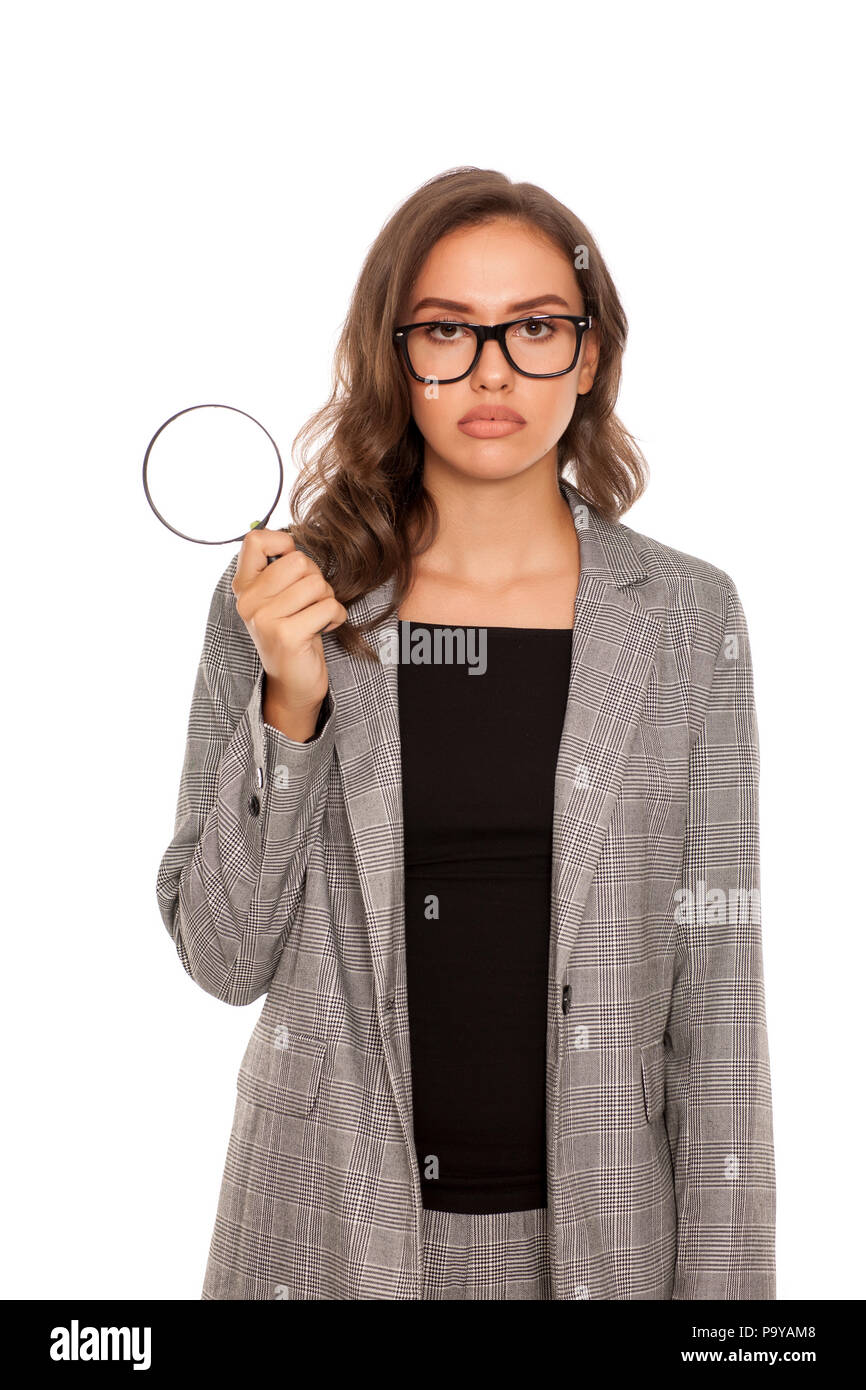Beautiful young unhappy woman looking trough the magnifying glass - Stock Image