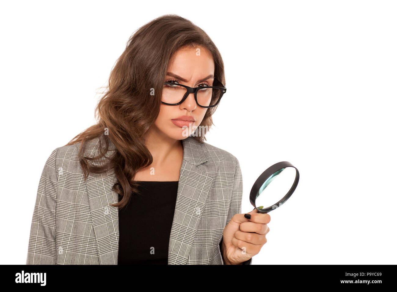 Beautiful young serious woman looking trough the magnifying glass Stock Photo