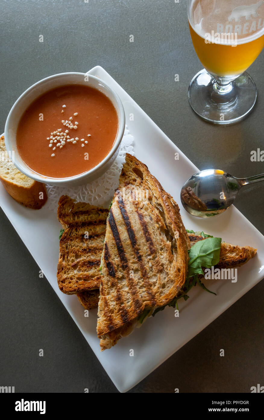 Toasted cheese sandwich with gazpacho and a blonde Canadian beer - Stock Image