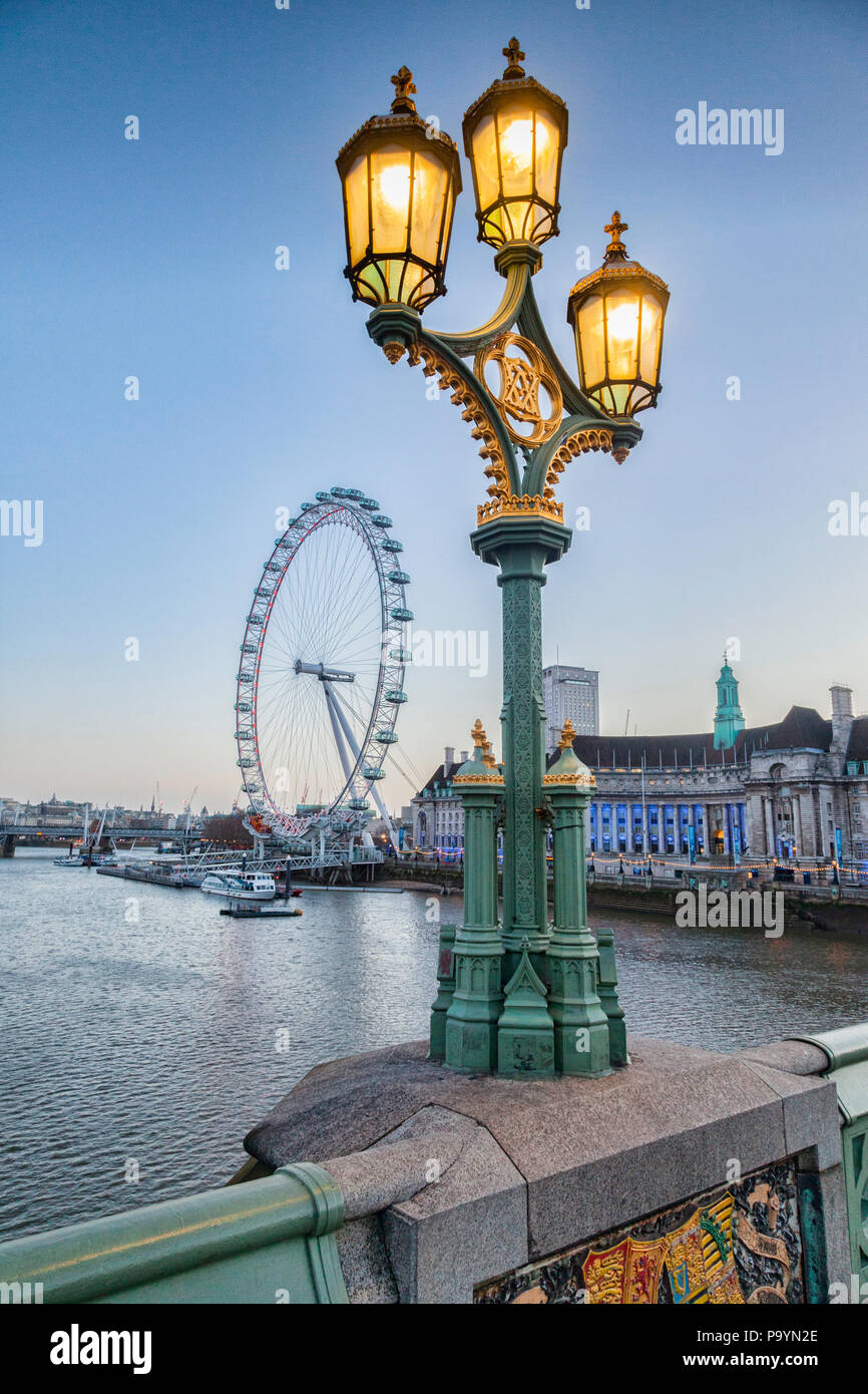 A lamp standard on Westminster bridge, illuminated, with the London Eye and County Hall in the background. - Stock Image