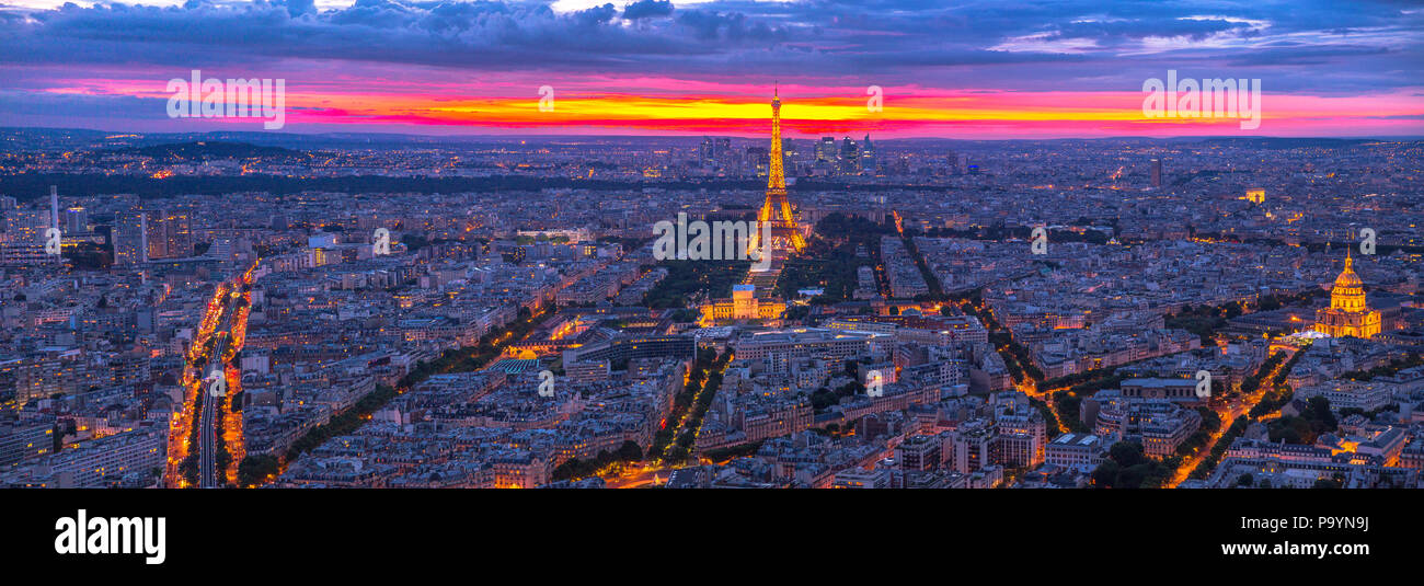 Paris, France - June 30, 2017: Tour Eiffel and national residence of the Invalids at twilight red sky panorama from Observatory Deck Tour Montparnasse. Aerial view of Paris skyline. Night urban scene. Stock Photo