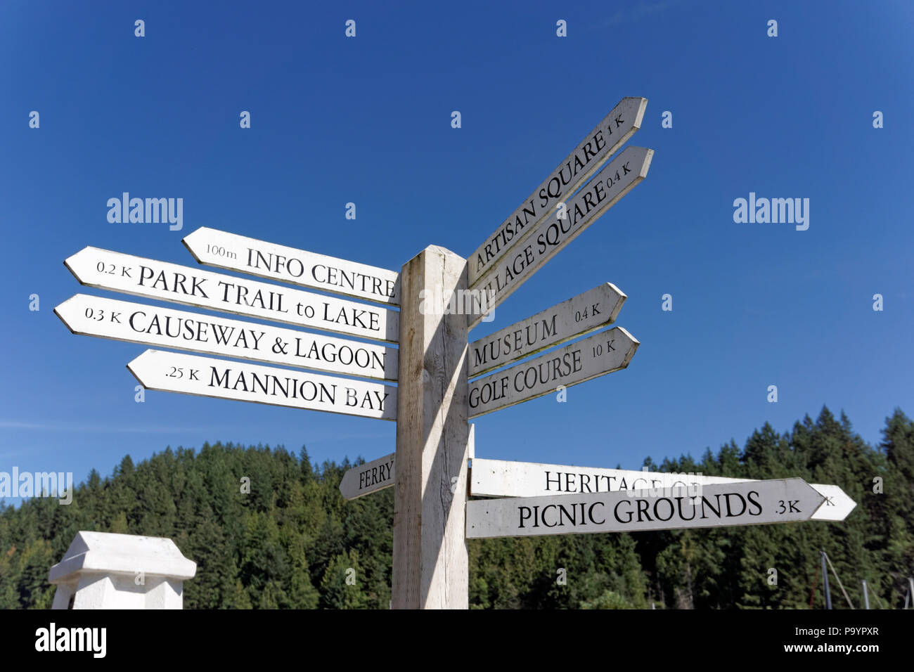 Wooden signpost showing direction and distance in kilometers to tourist attractions on Bowen Island near Vancouver, British Columbia, Canada - Stock Image