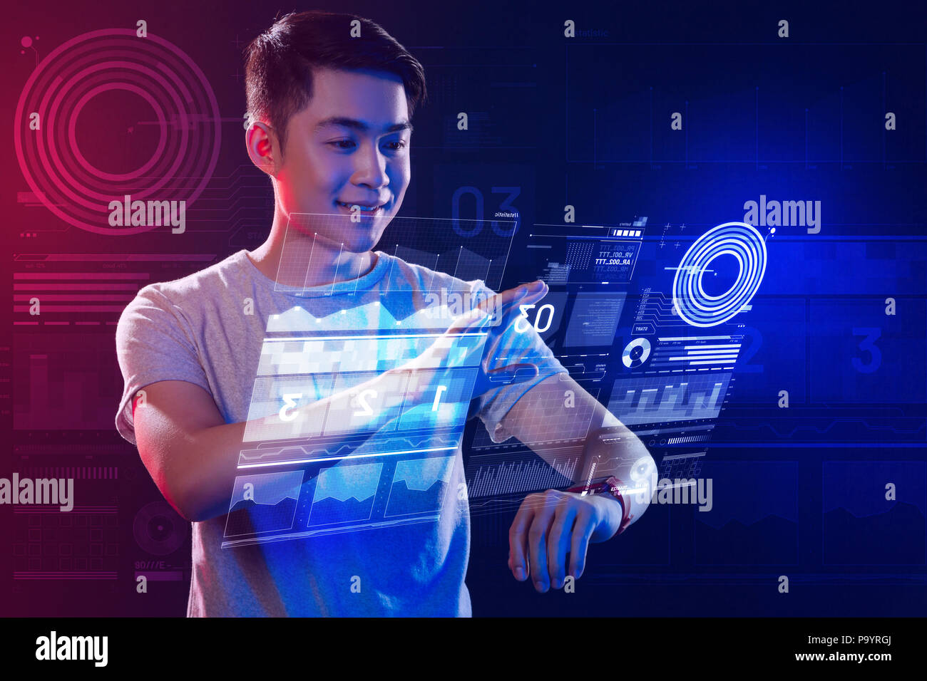 Positive web developer using a smartphone while working with holograms - Stock Image