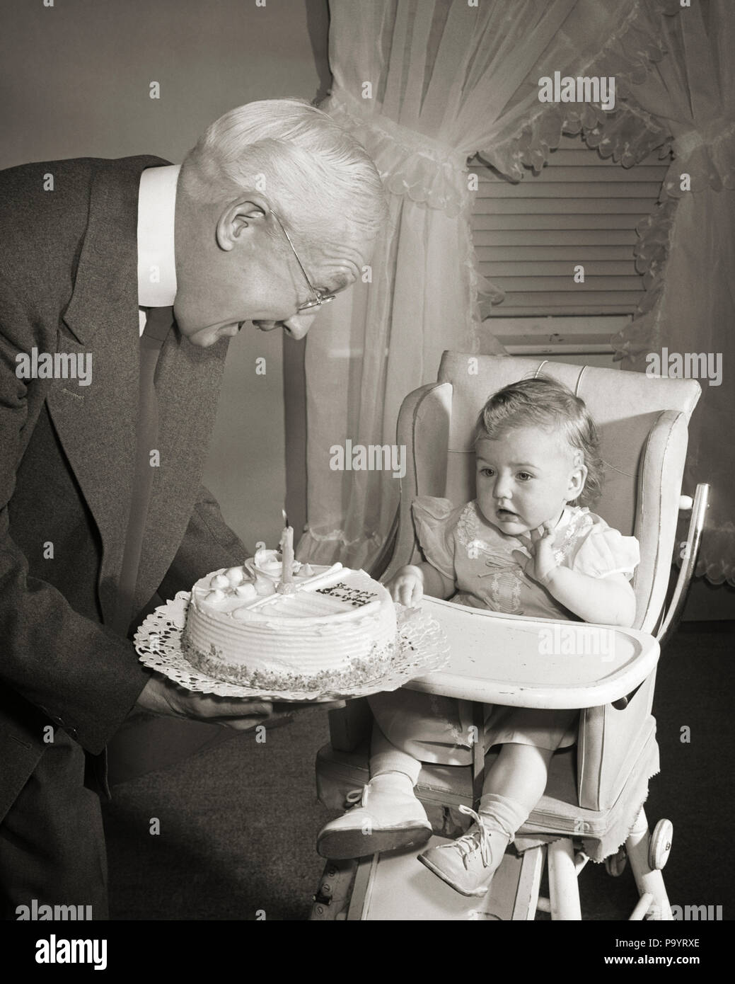 1950s SMILING GRANDFATHER PRESENTING BIRTHDAY CAKE WITH ONE YEAR CANDLE TO GRANDDAUGHTER SITTING IN HIGHCHAIR