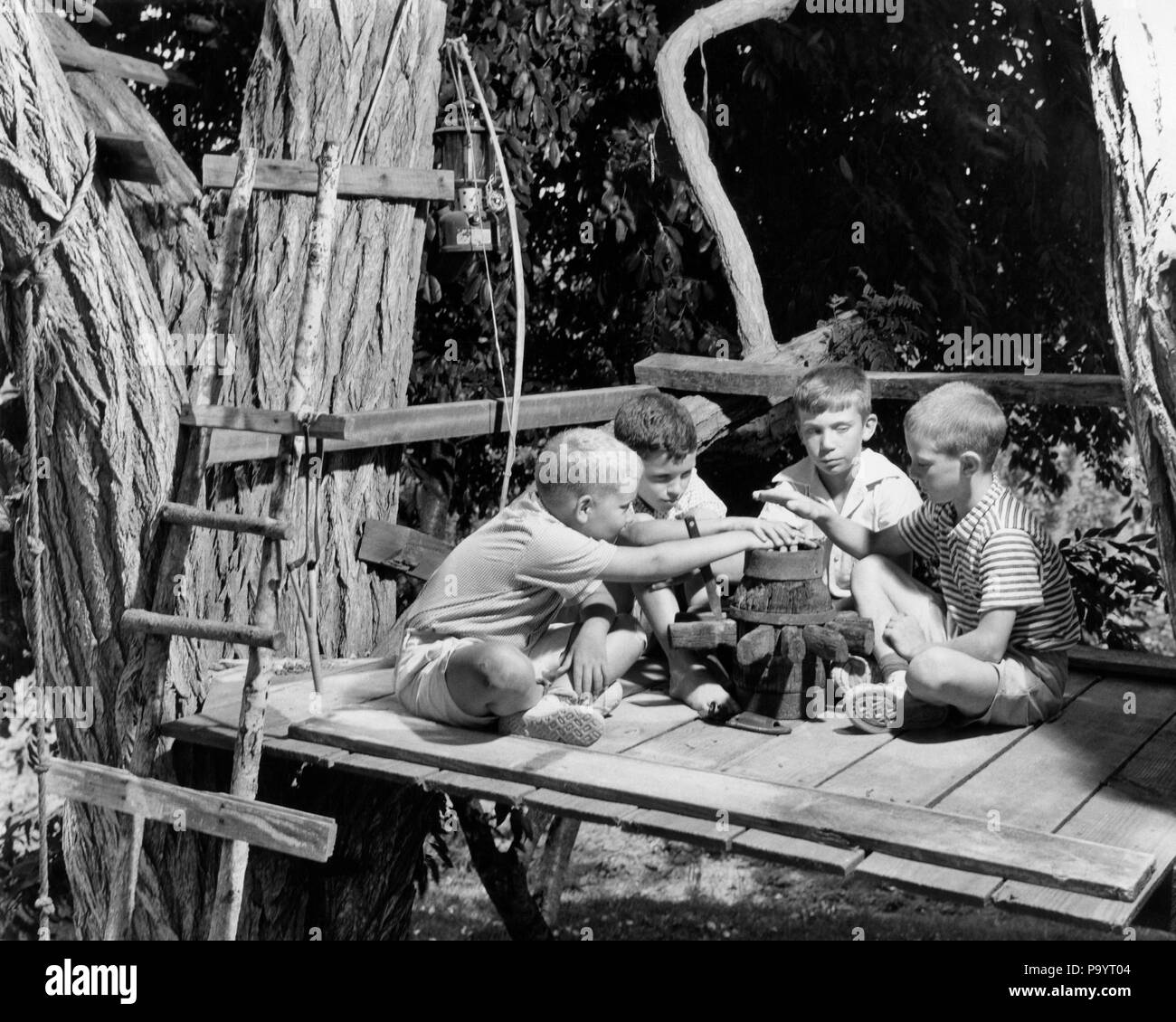 1950s 1960s FOUR BOYS IN TREE HOUSE CLUBHOUSE HOLDING HANDS OVER FAKE CAMPFIRE SWEARING TAKING OATH - b16212 CRS001 HARS EXCITEMENT CONNECTION OATH CLUBHOUSE IMAGINATION SWEARING GROWTH JUVENILES PRE-TEEN PRE-TEEN BOY TOGETHERNESS BLACK AND WHITE CAUCASIAN ETHNICITY OLD FASHIONED TREE HOUSE - Stock Image