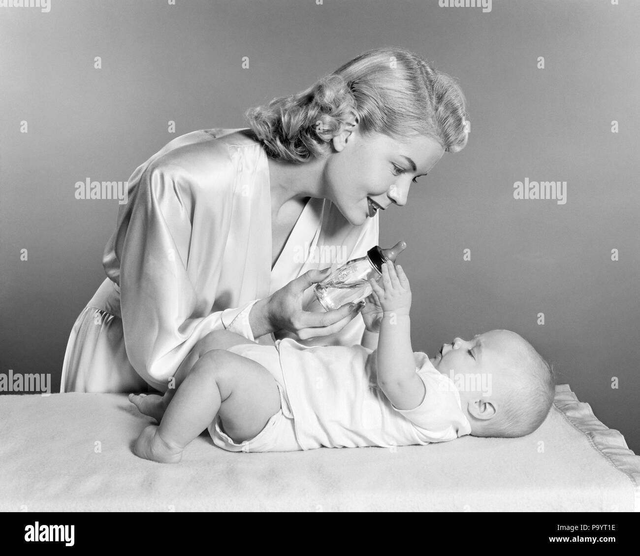1950s Smiling Blond Woman Mother Wearing Dressing Gown Giving Baby