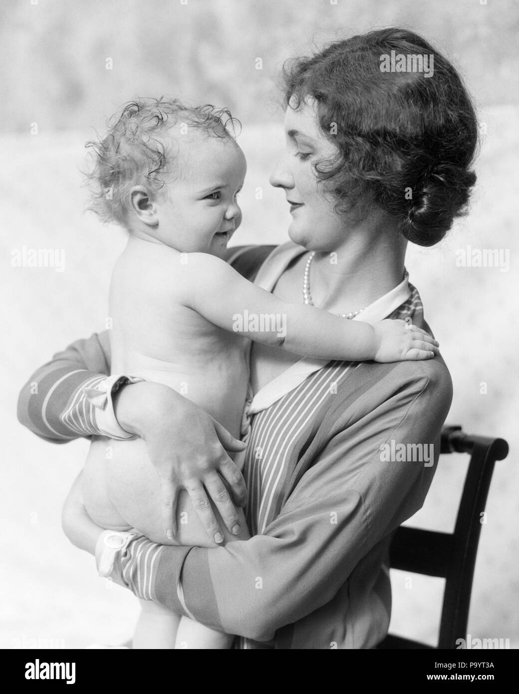 1920s WOMAN MOTHER SITTING IN CHAIR HOLDING SMILING BABY IN ARMS - b6492 HAR001 HARS YOUNG ADULT PLEASED JOY LIFESTYLE FEMALES PROUD HEALTHINESS HOME LIFE HALF-LENGTH LADIES DAUGHTERS PERSONS INSPIRATION CARING CONFIDENCE EMBRACING B&W BRUNETTE HAPPINESS WELLNESS CHEERFUL IN SMILES FACE TO FACE CONNECTION JOYFUL STYLISH JUVENILES MOMS TOGETHERNESS YOUNG ADULT WOMAN BLACK AND WHITE CAUCASIAN ETHNICITY HAR001 OLD FASHIONED Stock Photo