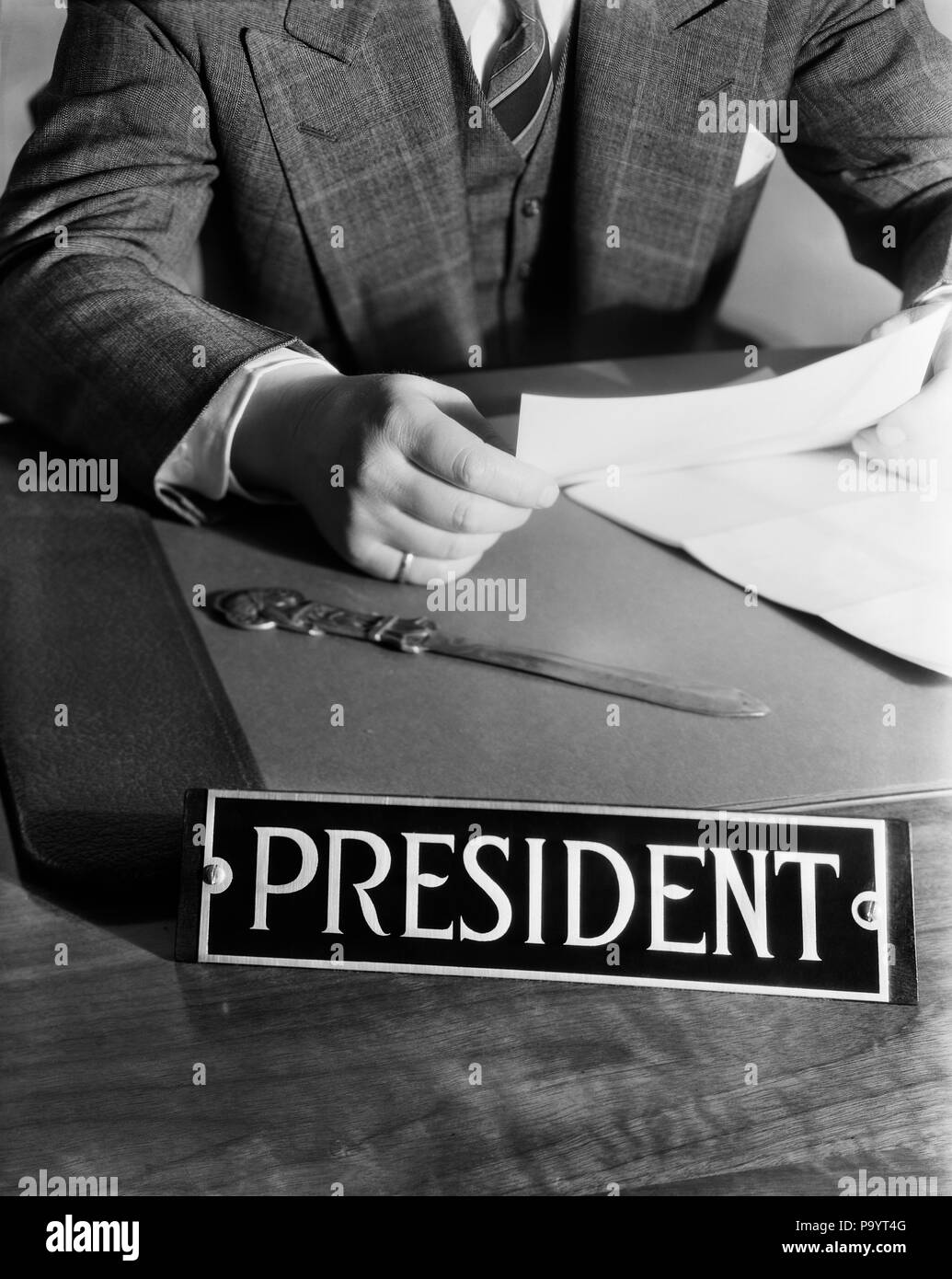 1930s 1940s 1950s MAN SITTING AT DESK READING LETTER WITH SIGN PRESIDENT - bx005410 CAM001 HARS LEADERSHIP CAM001 OPENER AUTHORITY CEO OCCUPATIONS PRESIDENTS BOSSES RESPONSIBILITY TITLE ANONYMOUS SYMBOLIC MANAGERS BLACK AND WHITE CAUCASIAN ETHNICITY CORPORATION NECK DOWN OLD FASHIONED - Stock Image