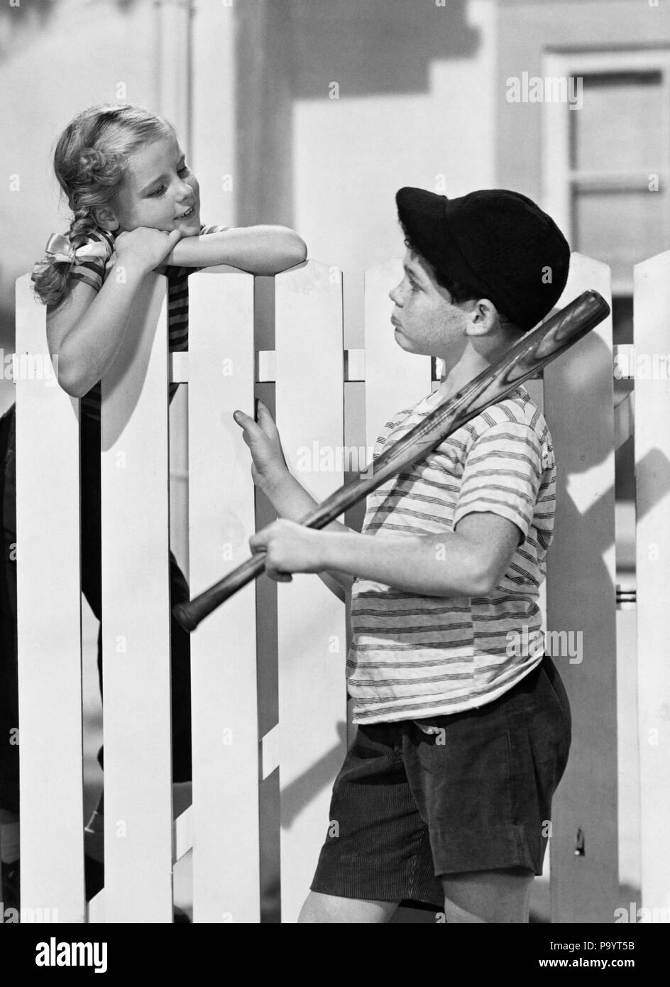 1940s 1950s BOY BASEBALL BAT CAP TALKING TO GIRL OVER WHITE PICKET FENCE - bx012617 CAM001 HARS FEMALES VERTICAL BROTHERS HOME LIFE COPY SPACE PEOPLE CHILDREN FRIENDSHIP HALF-LENGTH ADOLESCENT BOYFRIEND MALES SIBLINGS SISTERS B&W NEIGHBORS GIRLFRIEND PRETEEN BOY DREAMS HAPPINESS NEIGHBORHOOD CAM001 PRETEEN SIBLING BOYFRIENDS GIRLFRIENDS CRUSH PUPPY LOVE AFFECTION JUVENILES PRE-TEEN PRE-TEEN BOY PRE-TEEN GIRL TOGETHERNESS BLACK AND WHITE CAUCASIAN ETHNICITY OLD FASHIONED - Stock Image