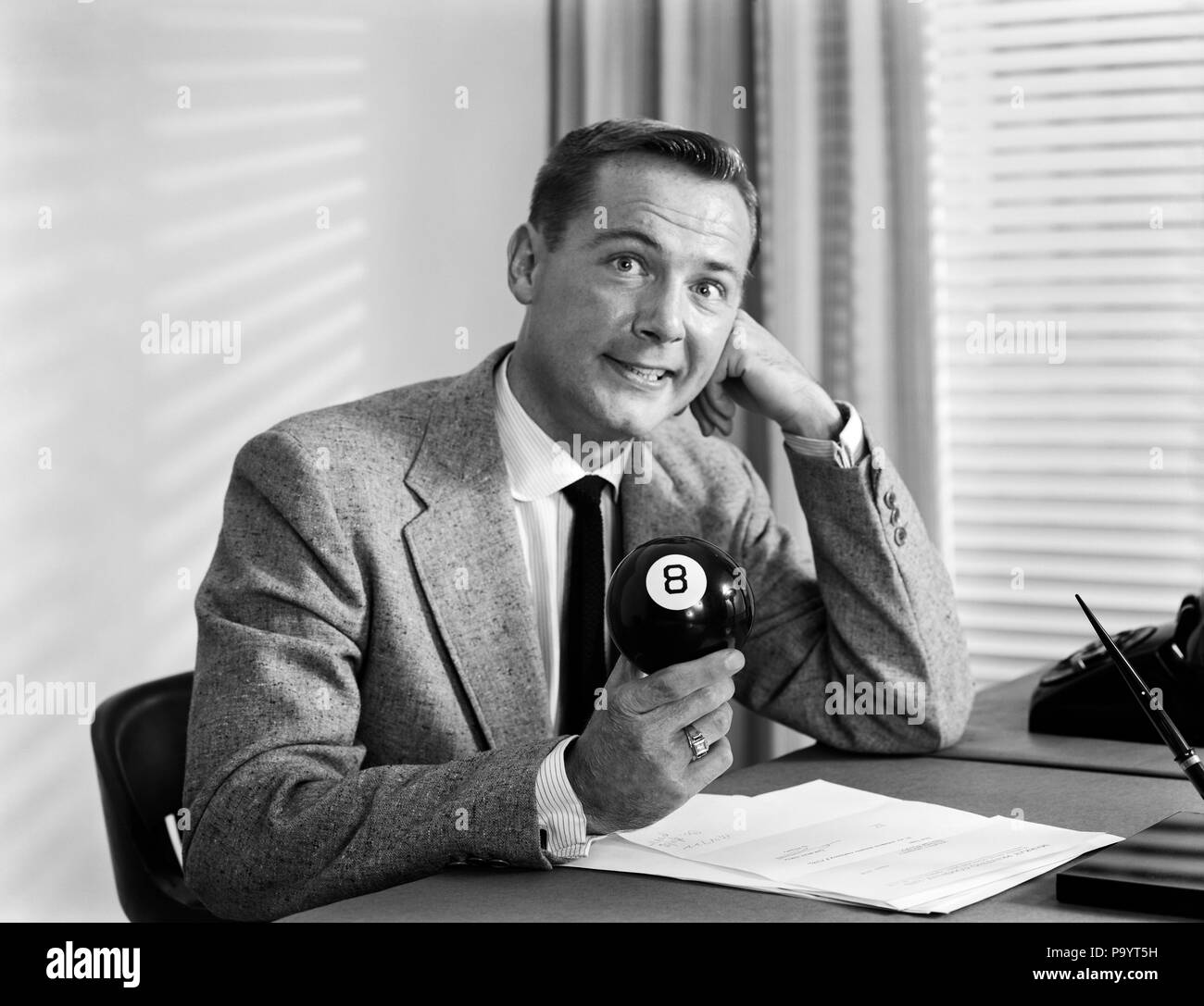 1950s WORRIED BUSINESSMAN SITTING AT DESK BEHIND BLACK EIGHT BALL LOOKING AT CAMERA - bx016818 CAM001 HARS RISK NERVOUS CORPORATE EXPRESSIONS B&W SUIT AND TIE SELLING 8 OBSTACLE CAM001 BILLIARDS DISADVANTAGE ESCAPE STUMPED NO ESCAPE DIFFICULTY EIGHT MID-ADULT MID-ADULT MAN SALESMEN 8 BALL BLACK AND WHITE CAUCASIAN ETHNICITY EIGHT BALL OLD FASHIONED PERPLEXED - Stock Image