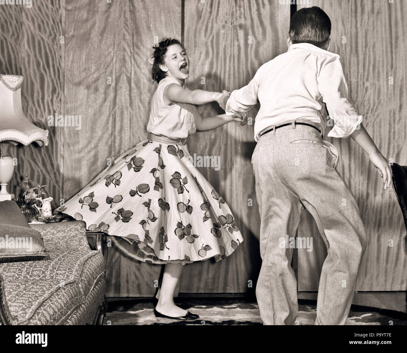 1950s TEENAGE COUPLE BOY AND GIRL DANCING ROCK AND ROLL JITTERBUG - d184 DEB001 HARS HOME LIFE FRIENDSHIP FULL-LENGTH ADOLESCENT PERSONS MALES TEENAGE GIRL TEENAGE BOY B&W JITTERBUG FREEDOM HAPPINESS AND EXCITEMENT RECREATION MOTION BLUR ESCAPE JOYFUL STYLISH TEENAGED DEB001 ROCK AND ROLL GROWTH JITTERBUGGING JUVENILES TOGETHERNESS BLACK AND WHITE CAUCASIAN ETHNICITY OLD FASHIONED - Stock Image
