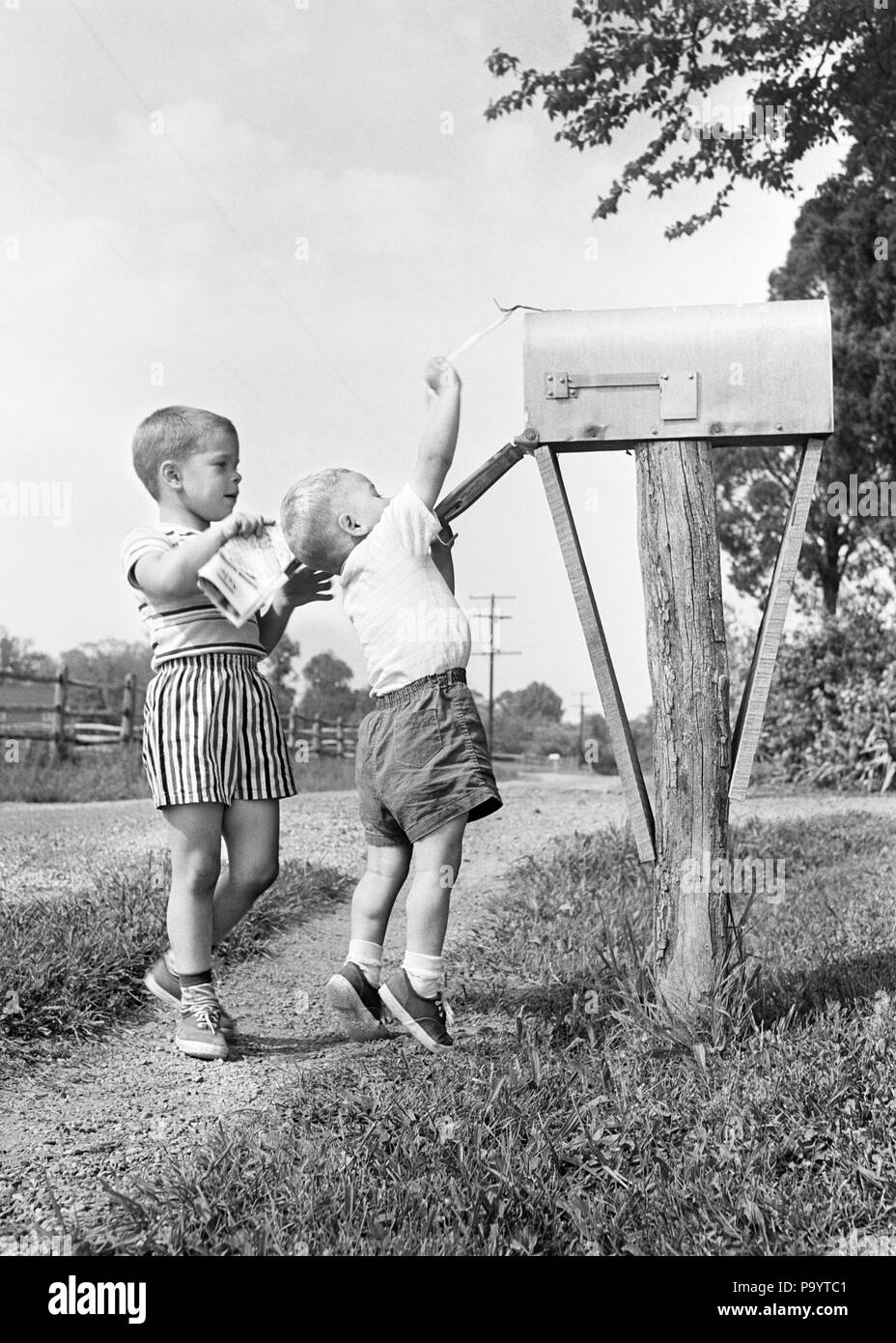 1950s TWO BOYS MAILING LETTERS RURAL COUNTRY ROAD - j2872 HBB001 HARS RFD SIBLING MAILING MAILBOX RURAL FREE DELIVERY COOPERATION GROWTH JUVENILES TOGETHERNESS BLACK AND WHITE CAUCASIAN ETHNICITY OLD FASHIONED - Stock Image