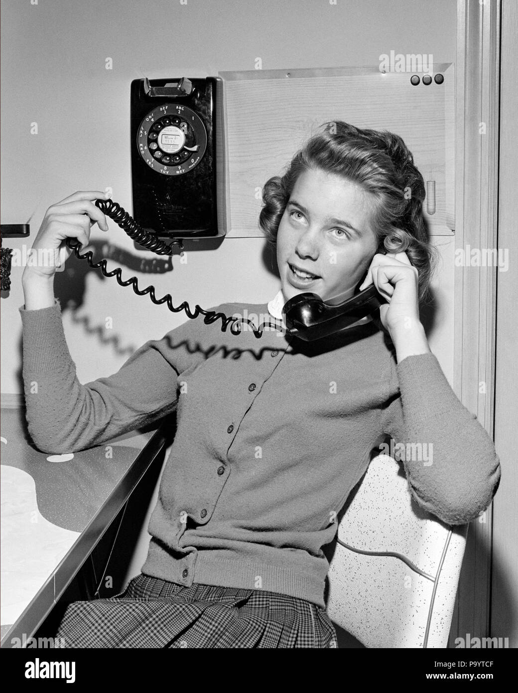 1950s TEENAGE GIRL TALKING ON WALL MOUNTED DIAL TELEPHONE HOLDING THE COILED PHONE CORD TO THE HANDSET - j9197 HAR001 HARS FRIENDSHIP HALF-LENGTH ADOLESCENT PERSONS TEENAGE GIRL ENTERTAINMENT GOSSIPING EXPRESSIONS B&W CORD FREEDOM DIAL HAPPINESS EXCITEMENT RECREATION HOPEFUL PHONES CONNECTION TELEPHONES COILED TEENAGED HANDSET JUVENILES MOUNTED BLACK AND WHITE CAUCASIAN ETHNICITY HAR001 OLD FASHIONED WALL PHONE - Stock Image