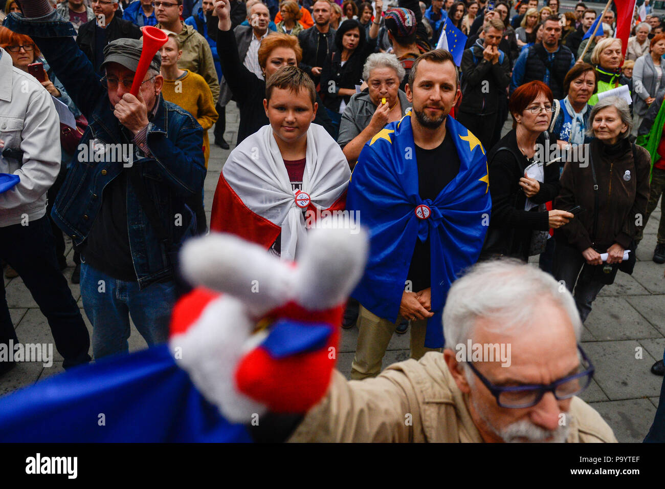 Two men seen covered in both Polish and European Union flags. People demonstrate against reforms of the Supreme Court and demand for free courts in Krakow, Poland. - Stock Image