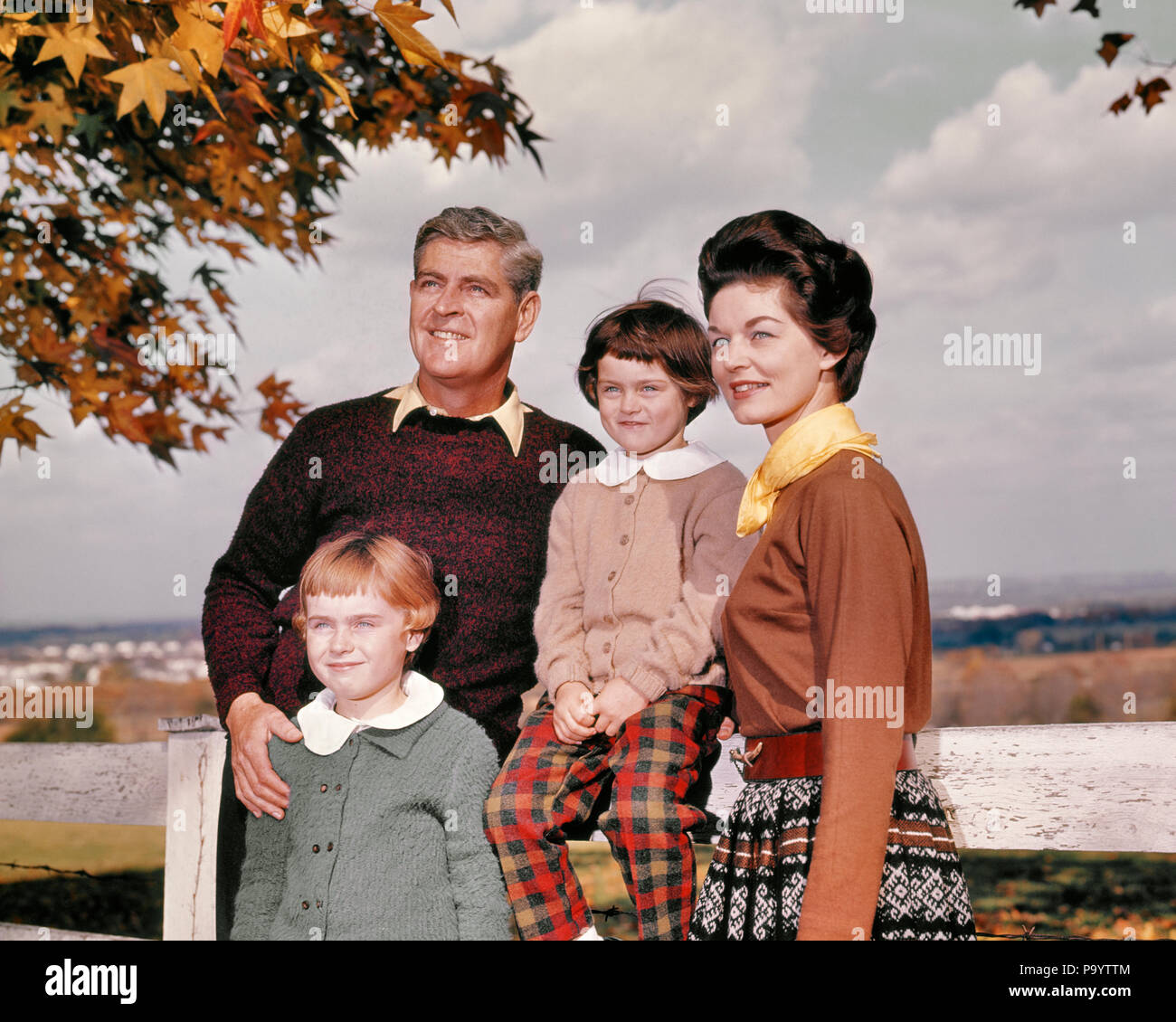 1960s FAMILY PORTRAIT OUTDOORS AUTUMN STANDING BY WHITE FENCE - kj1599 HAR001 HARS PAIR 4 LEAVES SUBURBAN COLOR RELATIONSHIP MOTHERS OLD TIME NOSTALGIA OLD FASHION SISTER 1 JUVENILE STYLE YOUNG ADULT PLEASED FAMILIES JOY LIFESTYLE FEMALES RURAL HEALTHINESS HOME LIFE NATURE COPY SPACE HALF-LENGTH LADIES DAUGHTERS PERSONS MALES SIBLINGS SISTERS FATHERS MIDDLE-AGED MIDDLE-AGED MAN HAPPINESS CHEERFUL DADS FALL SEASON PRIDE SIBLING SMILES CONNECTION JOYFUL RELATED STYLISH COOPERATION GROWTH JUVENILES MID-ADULT MID-ADULT WOMAN MOMS TOGETHERNESS AUTUMNAL CAUCASIAN ETHNICITY FALL FOLIAGE HAR001 - Stock Image