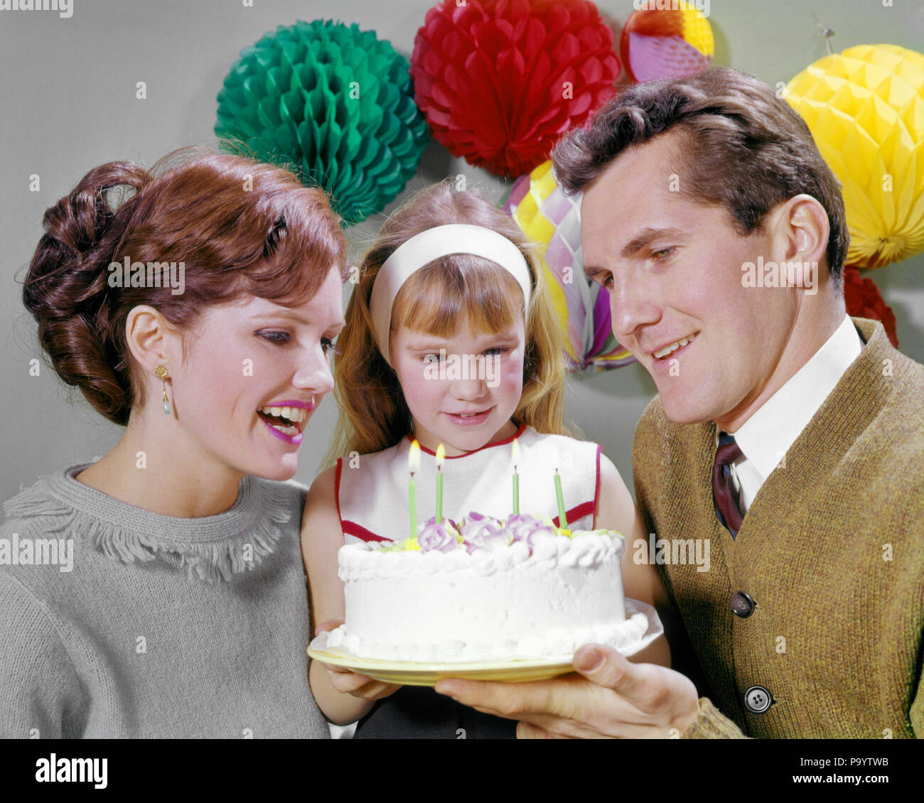 1960s SMILING MOTHER AND FATHER WITH DAUGHTER READY TO BLOW OUT CANDLES ON BIRTHDAY CAKE PARTY DECORATIONS