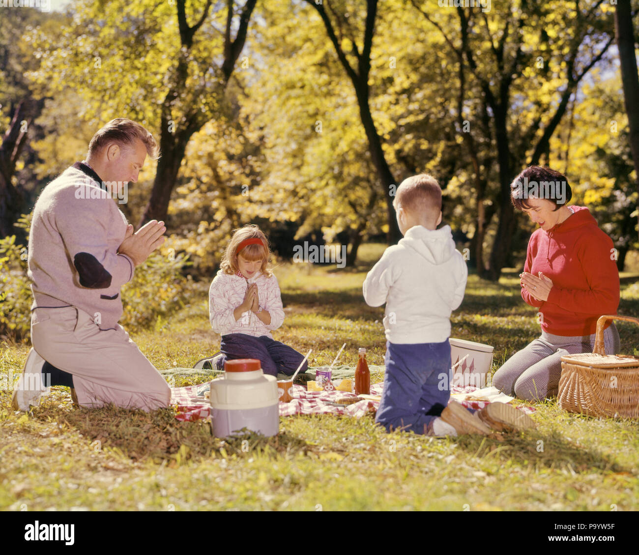 1960s FAMILY KNEELING AROUND PICNIC IN GRASS AUTUMN DAY