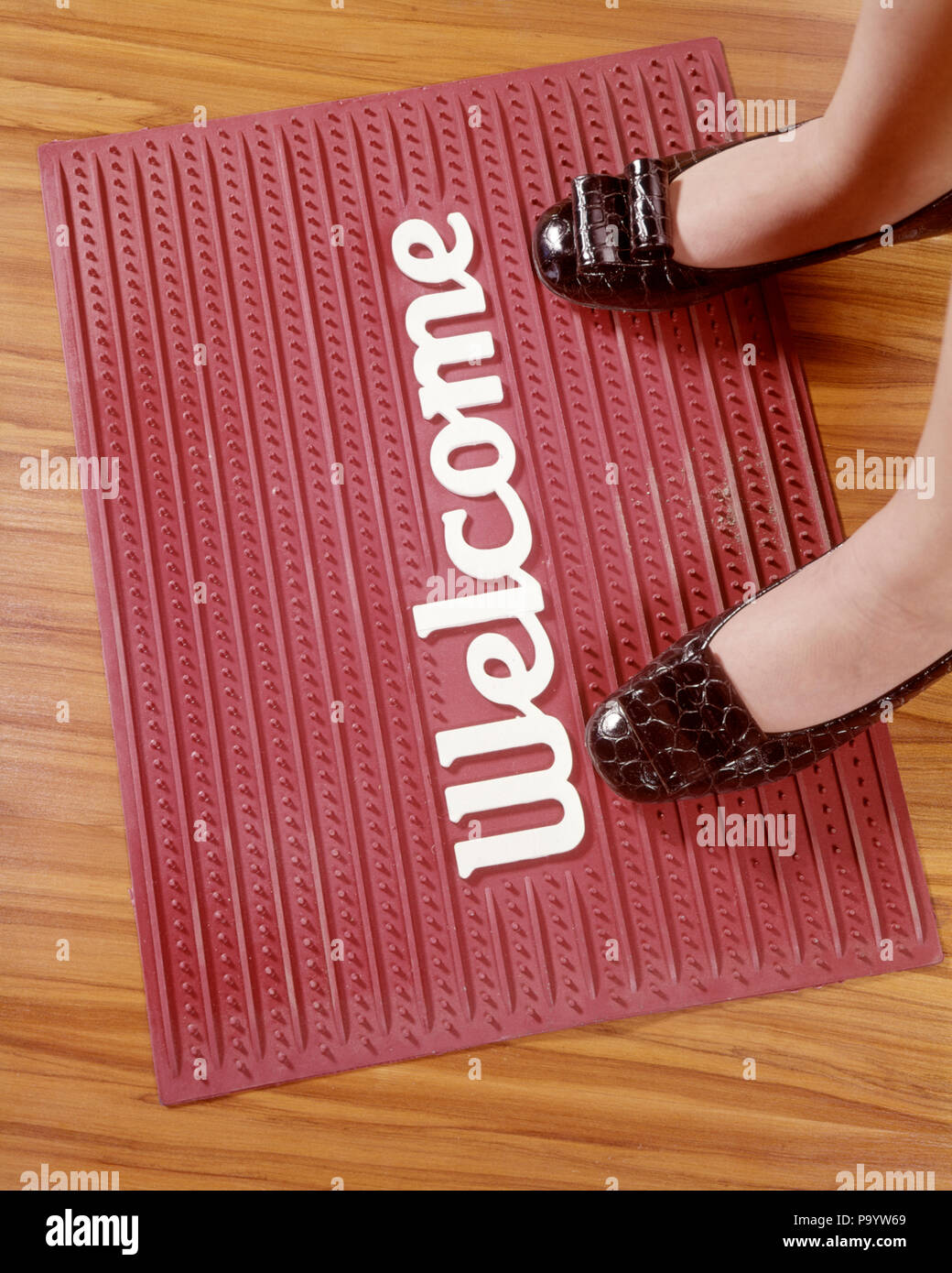 1970s WOMAN FEET BLACK SHOES ON RED RUBBER WELCOME MAT  - ks6441 HAR001 HARS HIGH ANGLE CUSTOMER SERVICE EQUAL PAY WORD ARRIVING OPPORTUNITY EMPLOYMENT OCCUPATIONS CONCEPT CONCEPTUAL GLASS CEILING SEXISM SYMBOLIC ARRIVAL DESTINATION DISCRIMINATION EQUALITY GENDER CAUCASIAN ETHNICITY HAR001 OLD FASHIONED REPRESENTATION - Stock Image