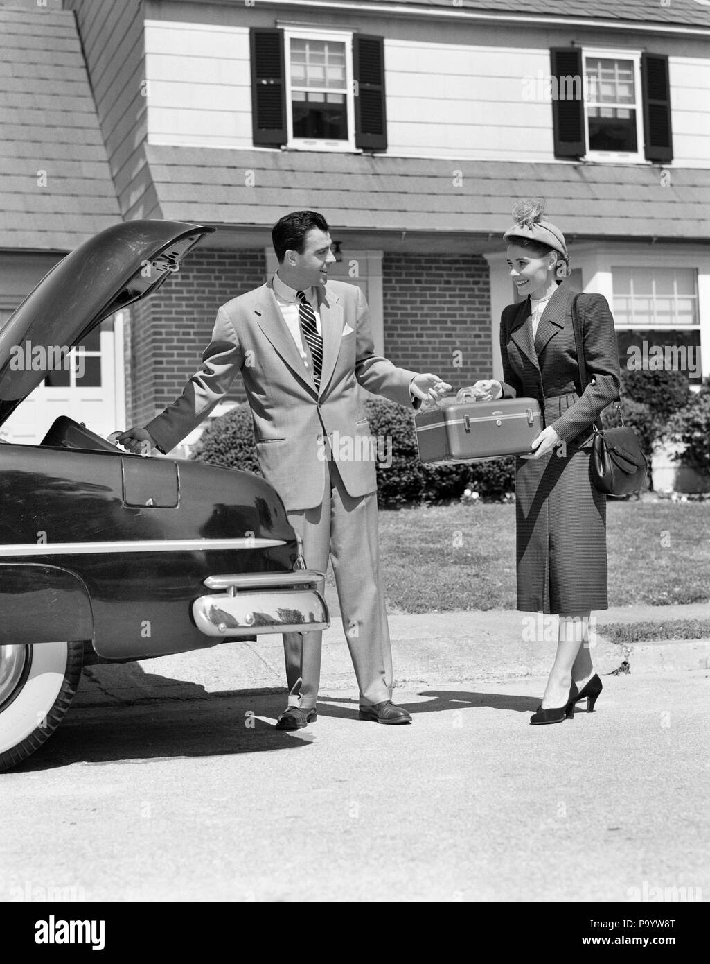 1950s COUPLE PACKING LUGGAGE IN CAR TRUNK FOR VACATION TRIP - m3529 HAR001 HARS SPOUSE HUSBANDS HOME LIFE TRANSPORT COPY SPACE FRIENDSHIP FULL-LENGTH LADIES PERSONS AUTOMOBILE MALES TRUNK BUILDINGS TRANSPORTATION B&W STRUCTURE HAPPINESS ADVENTURE PROPERTY STYLES MOTOR VEHICLE TRIP AUTOS EXCITEMENT MOTORING AUTOMOBILES STYLISH VEHICLES EDIFICE FASHIONS MID-ADULT MID-ADULT MAN MID-ADULT WOMAN TOGETHERNESS WIVES BLACK AND WHITE CAUCASIAN ETHNICITY HAR001 OLD FASHIONED - Stock Image