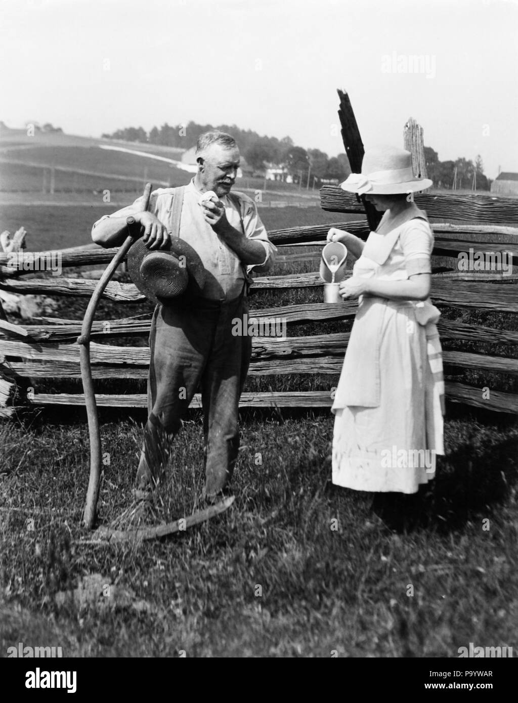 1890s 1900s 1910s WOMAN STRAW HAT APRON POURING GLASS MILK WATER FOR FARMER STANDING SWEATING BY FENCE LEANING ON SCYTHE - o6374 HAR001 HARS TOOL OLD FASHION STYLE FEMALES MARRIED RURAL HEAT SPOUSE HUSBANDS HEALTHINESS HOME LIFE COPY SPACE FRIENDSHIP FULL-LENGTH LADIES DRY PERSONS CARING FARMING MALES SWEAT SENIOR MAN SWEATING AGRICULTURE B&W SUMMERTIME PITCHER TURN OF THE 20TH CENTURY FARMERS SCYTHE STRAW HAT NOURISHMENT SUPPORT COURTESY REFRESH MID-ADULT WOMAN PERSPIRATION REFRESHMENT RELIEF THIRST THIRSTY TOGETHERNESS WIVES WOODEN FENCE BLACK AND WHITE CAUCASIAN ETHNICITY HAR001 - Stock Image