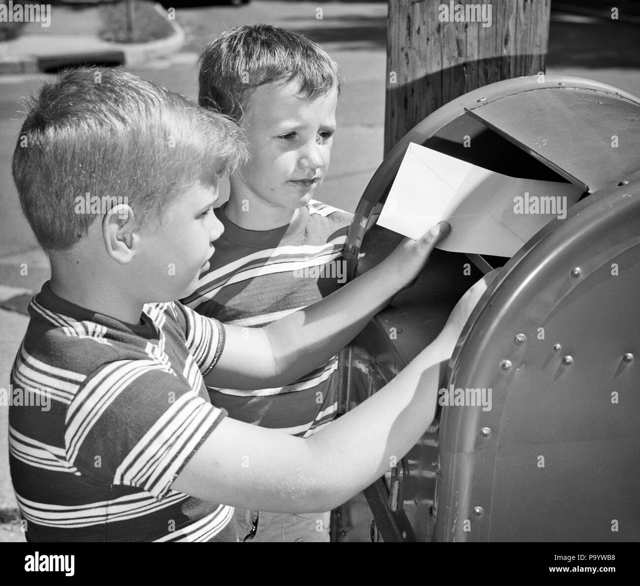 1960s 1970s TWO BOYS MAILING LETTER IN MAILBOX - p7771 HAR001 HARS HAR001 OLD FASHIONED - Stock Image