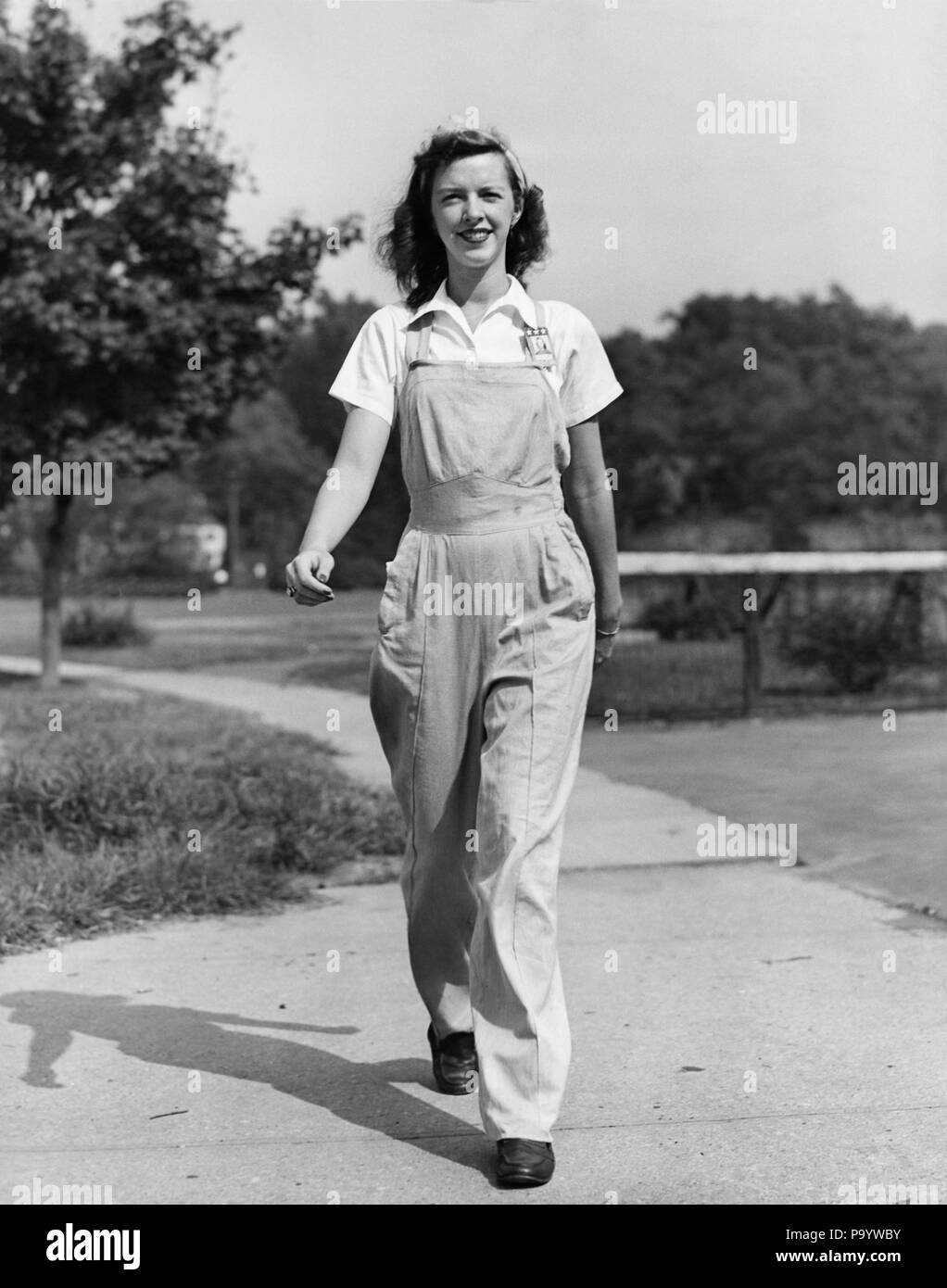 1940s HAPPY SMILING WOMAN FEMALE WORKER OUTDOOR WALKING TOWARD  WEARING BIB OVERALLS COVERALLS WORK CLOTHES LOOKING AT CAMERA - q43287 CPC001 HARS GROWING YOUNG ADULT PLEASED JOY LIFESTYLE FEMALES WW2 RURAL GROWNUP HOME LIFE COMMUNICATING FULL-LENGTH LADIES PHYSICAL FITNESS PERSONS OVERALLS GROWN-UP FARMING CONFIDENCE AGRICULTURE B&W EYE CONTACT OCCUPATION CHEERFUL STRENGTH TOWARD WORLD WARS INDEPENDENT WORLD WAR WORLD WAR TWO WORLD WAR II SMILES GROW JOYFUL ROSIE THE RIVETER STYLISH WORLD WAR 2 BIB COMMUNICATE YOUNG ADULT WOMAN BLACK AND WHITE CAUCASIAN ETHNICITY COVERALLS OLD FASHIONED - Stock Image
