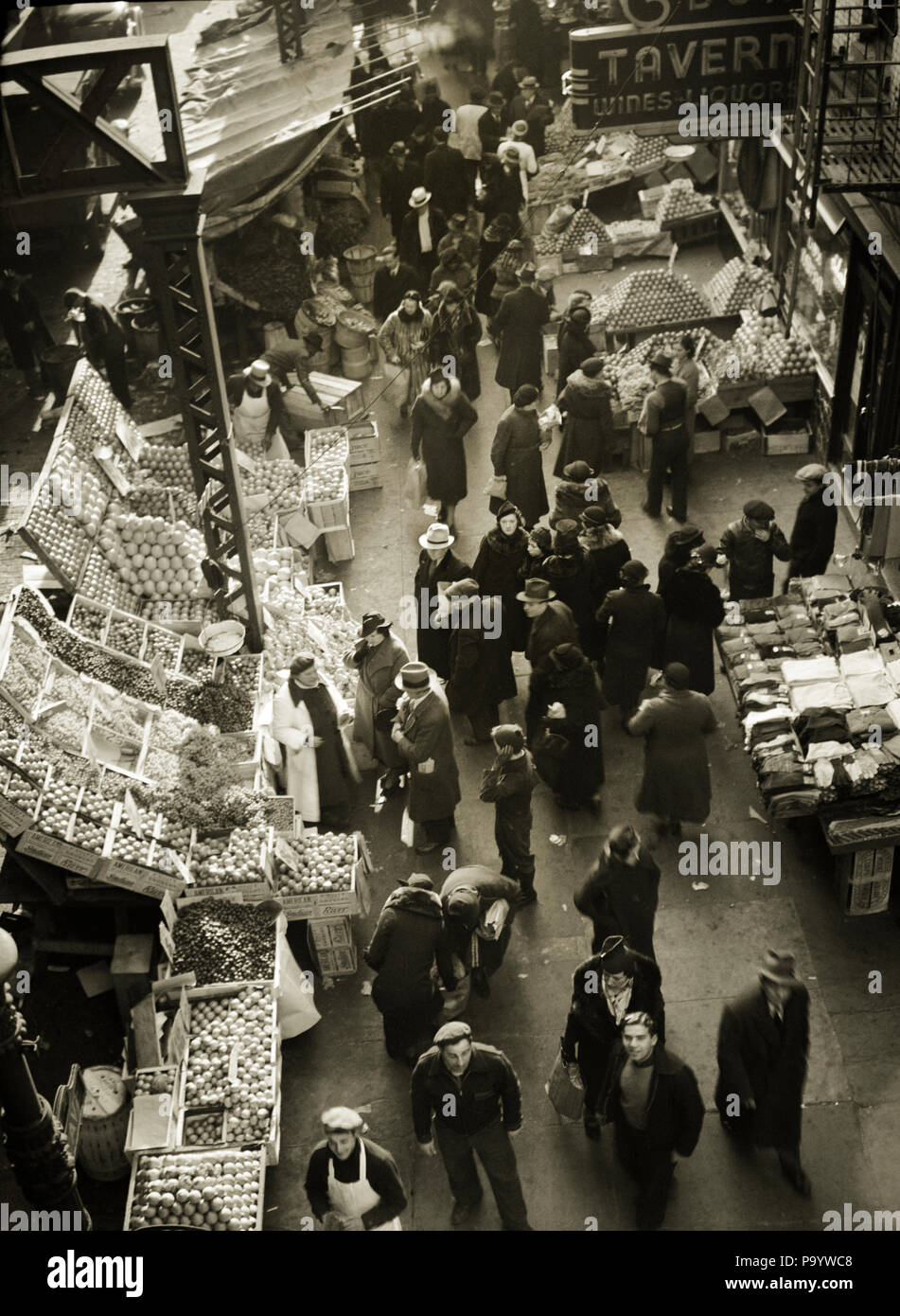 1930s 1937 FRUIT AND VEGETABLE MARKET STANDS ON SIDEWALKS OF WEST SIDE 9TH AVENUE IN HELLS KITCHEN NEW YORK CITY USA - q43698 CPC001 HARS CUSTOMER SERVICE MARKETS NYC SIDEWALKS NEW YORK CITIES NOURISHMENT PRODUCE NEW YORK CITY STANDS 9TH AVENUE FRUITS GREEN GROCERS HELLS KITCHEN 1937 AERIAL VIEW BLACK AND WHITE DISPLAYS OLD FASHIONED WEST SIDE - Stock Image