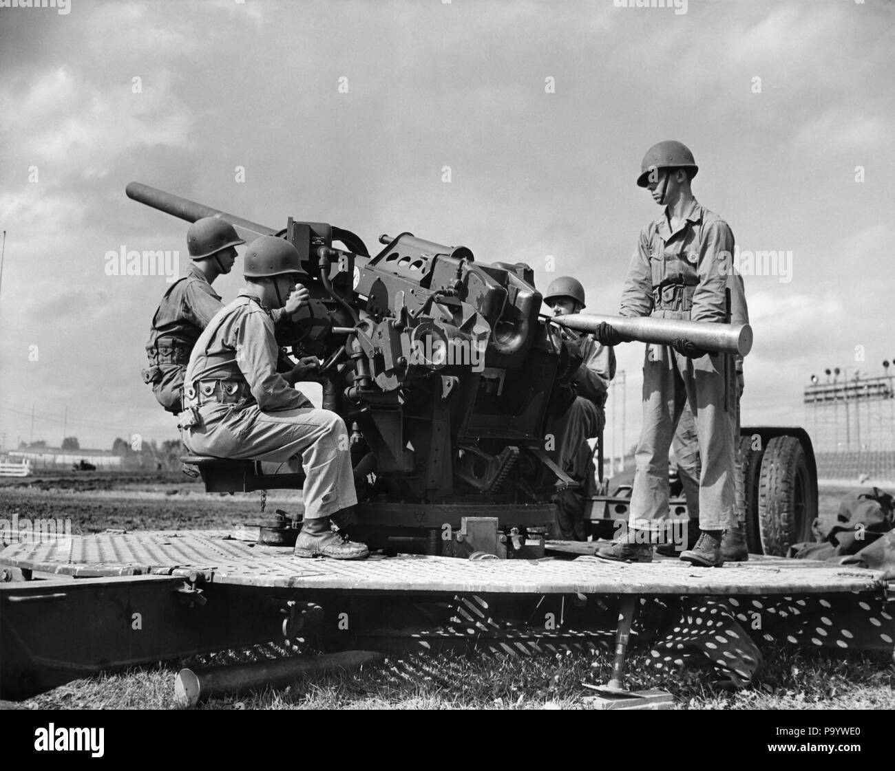 1940s CREW OF FOUR WORLD WAR II SOLDIERS MANNING ARTILLERY CANNON LOADING SHELL INTO BREECH OF GUN - q74716 CPC001 HARS LOADING STRENGTH COURAGE TRIO WORLD WARS WORLD WAR WORLD WAR TWO WORLD WAR II INTO OCCUPATIONS UNIFORMS WORLD WAR 2 AMMUNITION MANNING CONFLICTING FIREARM YOUNG ADULT MAN ARTILLERY BATTLING BLACK AND WHITE CAUCASIAN ETHNICITY OLD FASHIONED - Stock Image